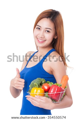 Smiling young woman with a fresh vegetables and showing thumb up. healthy concept