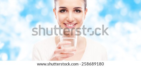 Smiling young woman with a glass drinking water, purity and wellbeing concept - stock photo