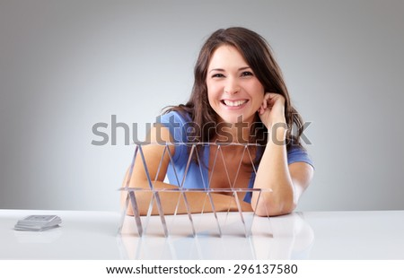 Smiling young woman with a house of cards on isolated background - stock photo