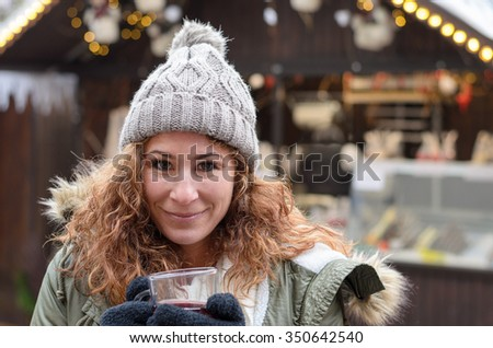 Smiling young woman with a mulled wine in her hands while she is standing on a Christmas Market - stock photo