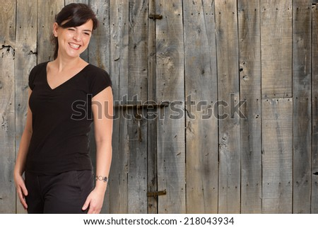 Smiling young woman with a rural door - stock photo