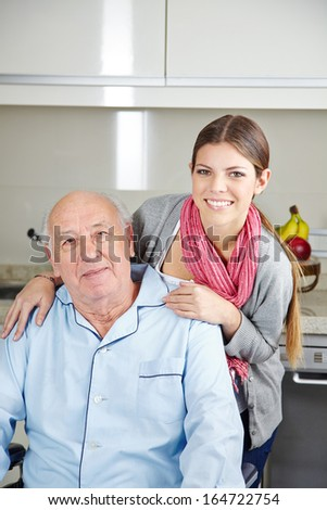 Smiling young woman with a senior man in a wheelchair - stock photo