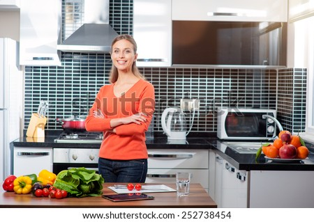 Smiling young woman with arms crossed in the kitchen with vegetables - stock photo