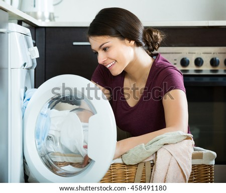 Smiling young woman with basket of sheets near washing machine indoors