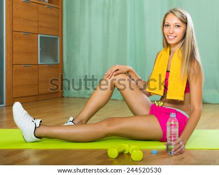Smiling young woman with bottle of water after exercising indoor  - stock photo