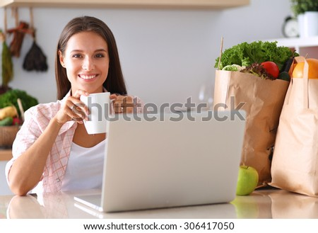 Smiling young woman with coffee cup and laptop in the kitchen at home . - stock photo