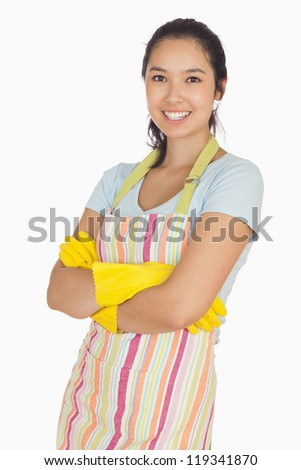 Smiling young woman with crossed arms wearing rubber gloves and apron - stock photo