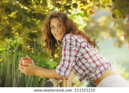 Smiling young woman with cup of coffee  enjoy the sunrise - stock photo