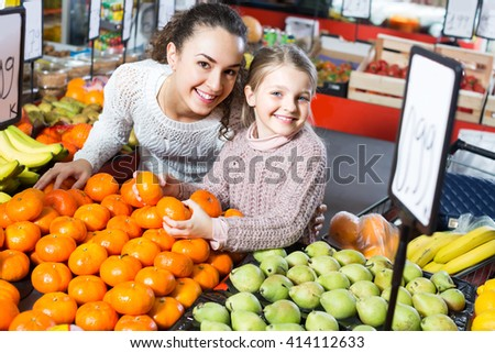 Smiling young woman with cute little daughter choosing fruits at market