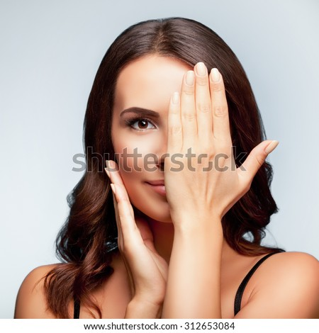 smiling young woman, with eye, clossed by hand, covering part of her face, over bright grey background, square composition - stock photo