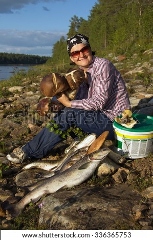 Smiling young woman with gifts of the nature sits on the bank of the northern river. Kola Peninsula, Russia.