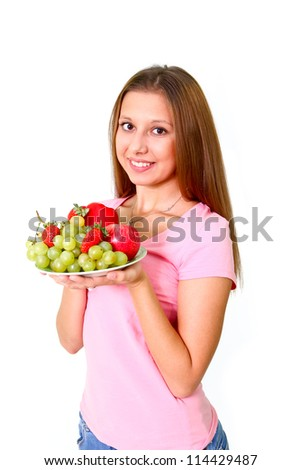 Smiling young woman with grapes, apples and strawberries on a dish