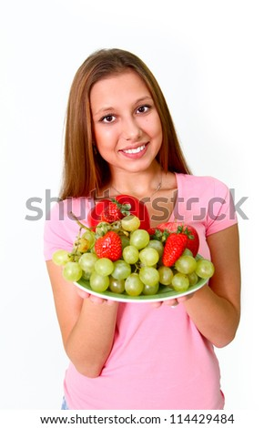 Smiling young woman with grapes, apples, pepper and strawberries on a dish