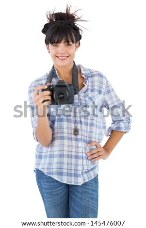 Smiling young woman with hand on her hip taking picture on white background