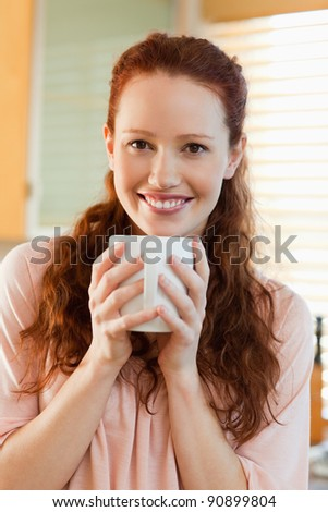 Smiling young woman with her cup of coffee - stock photo