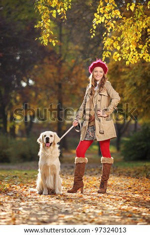 Smiling young woman with her labrador retreiver dog in a city park - stock photo