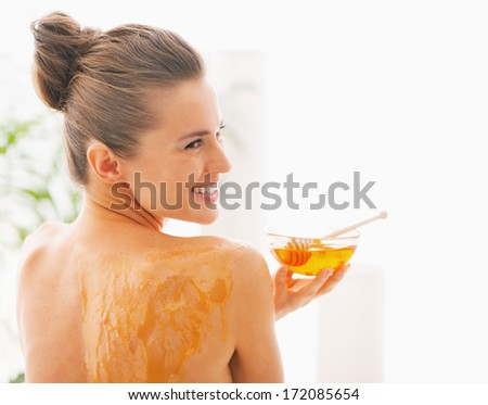 Smiling young woman with honey plate sitting on massage table