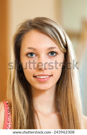 Smiling young woman with long blond hair in the room