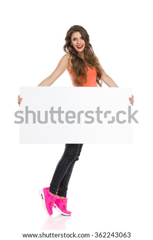 Smiling young woman with long hair orange shirt and pink sneakers standing tiptoe, holding blank placard and looking at camera. Full length studio shot isolated on white.