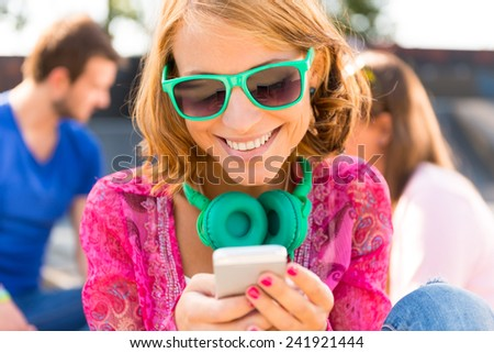 Smiling young woman with mobile phone - stock photo