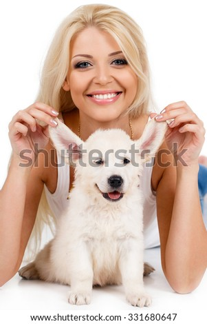 smiling young woman with pet puppy, studio shot. Close up of woman in white sweater with puppy of labrador