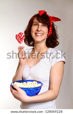 Smiling young woman with popcorn and lollipop - stock photo