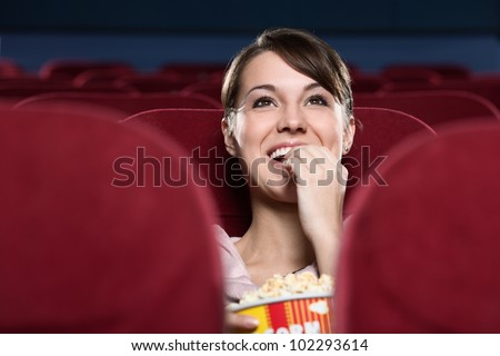 Smiling young woman with popcorn watching a movie - stock photo