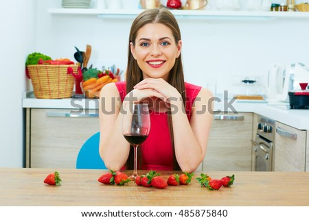 Smiling young woman with red wine glass sitting in kitchen.