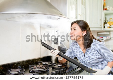 Smiling young woman with rubber gloves cleaning kitchen - stock photo