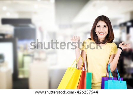 Smiling young woman with shopping bags over mall background with copy space.