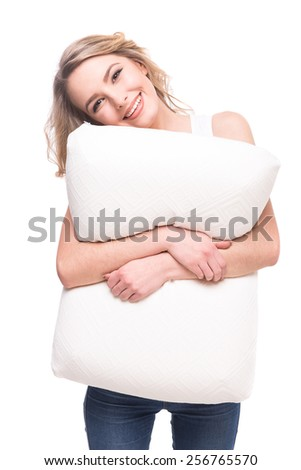 Smiling young woman with soft pillow is looking at the camera over white background. - stock photo