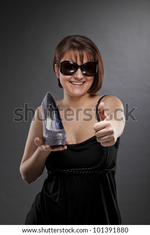 smiling young woman with sunglasses holding a shoe and posing with the thumbs up sign - stock photo