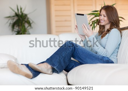 Smiling young woman with tablet on the sofa - stock photo