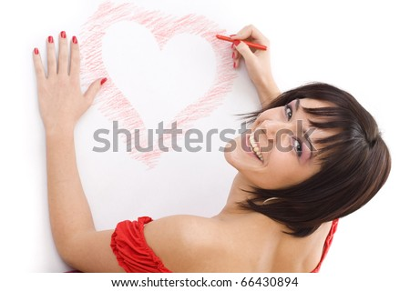 Smiling young woman with wax crayon lying on floor and drawing heart-shape - stock photo