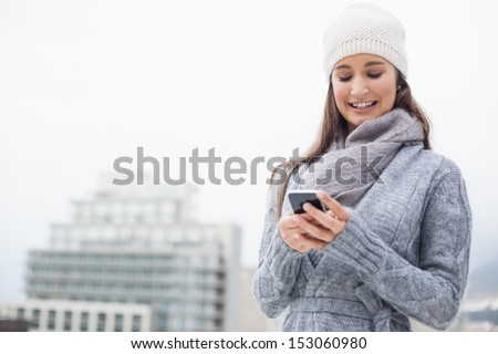 Smiling young woman with winter clothes on text messaging outdoors on a cold grey day - stock photo