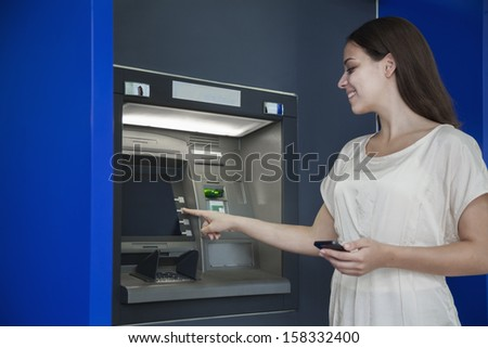 Smiling young woman withdrawing money from ATM - stock photo