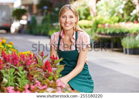 Smiling young woman working as gardener in a nursery shop - stock photo