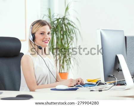 Smiling young woman working in a call center - stock photo