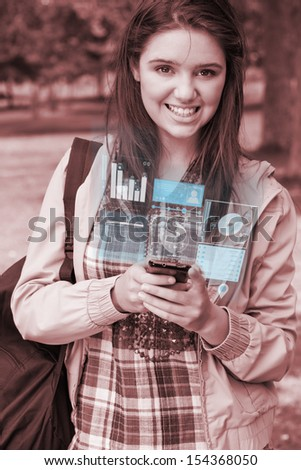 Smiling young woman working on her futuristic smartphone in bright park - stock photo