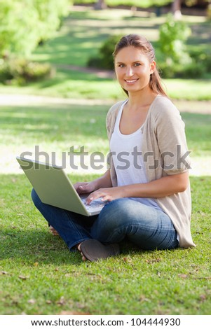 Smiling young woman working on her notebook in the park