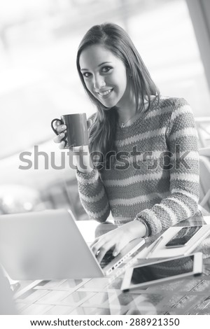 Smiling young woman working with her laptop and holding a mug - stock photo