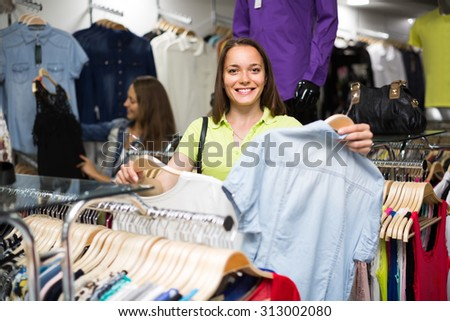 Smiling young women choosing blouse in clothing store