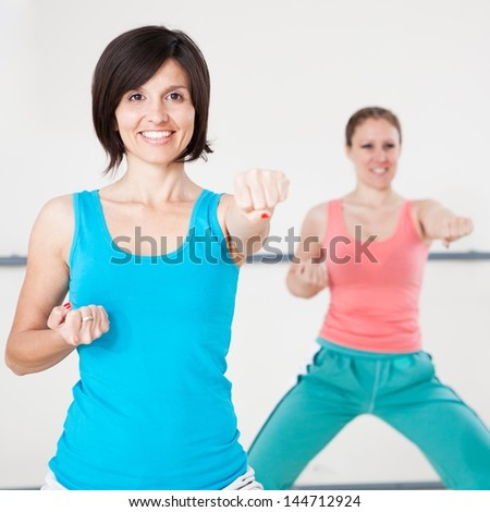Smiling young women doing a punching exercise during a fitness class in the gym, looking at camera.