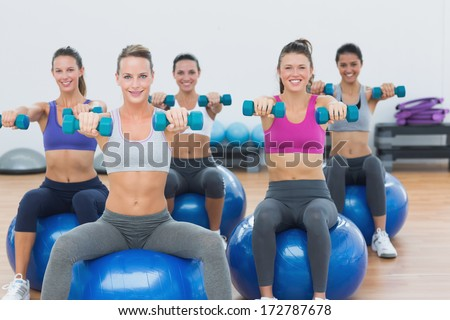 Smiling young women exercising with dumbbells on fitness balls in gym - stock photo