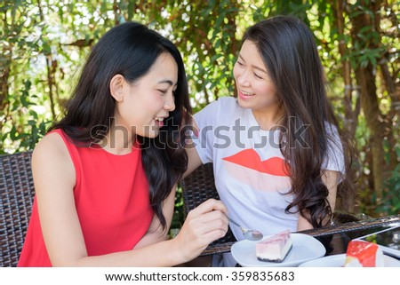 Smiling young women friends talking at outdoor cafe - communication and friendship concept