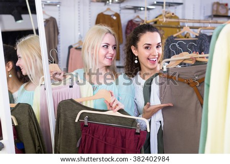 Smiling young women shopping at the clothing store together