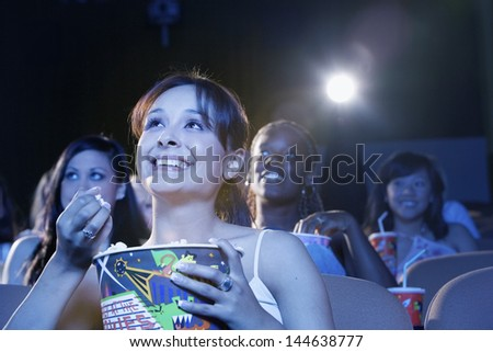 Smiling young women sitting and watching movie in the theatre