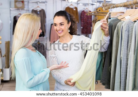 Smiling young women 25-30 years old shopping at the clothing store