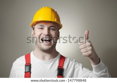 Smiling young worker with yellow hard hat - stock photo