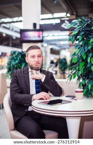 Smiling ypung businessman sitting, coffee, mobile - stock photo